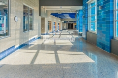 Grain Valley High School chose the Bomanite Modena SL Custom Polishing System to renovate the main entrance and hallways of the school and this stunning polished concrete surface features a mixture of blue glass and mirror glass aggregates that were incorporated to create a unique display of school pride.