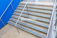 """The Bomanite Modena SL Custom Polishing System was utilized on several sets of concrete steps as a low maintenance option for Grain Valley High School and to create visual interest and display the school colors, the addition of the three-line nose detail was engraved into the concrete and filled with """"Grain Valley Blue"""" epoxy."""