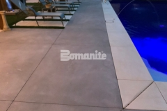 The installation of Bomanite Revealed decorative concrete in this outdoor space was the perfect choice to create a durable decking surface and the Antique White and Slate Gray color selection pairs well with the scattering of mirror glass, adding sparkle and sophistication.