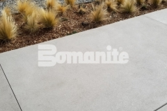 Bomanite Sandscape Refined Exposed Aggregate decorative concrete was utilized here to create this distinctive hardscape surface and the incorporation of white color hardener combined with locally sourced aggregates, mirror glass, and saw cuts perfectly complements the nautical themed design at the 50 Fifty DTC office complex.