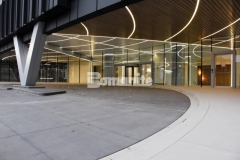The hardscape at 50 Fifty DTC features the Bomanite Sandscape Refined Exposed Aggregate System and the illuminated radial cut joints that were incorporated into the design radiate toward the building in diverging rays to imitate and complement the LED lights that were integrated overhead.