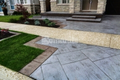This imprinted concrete driveway and patio were created using the Bomanite Yorkshire Stone imprint pattern in combination with Bomanite Shale Gray Color Hardener and a Gray Release Agent to add distinctive design detail and provide the beauty of natural paving with the durability and affordability of concrete.