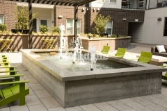 This stylish gathering space at the COLAB Co-Housing Development showcases a beautiful water fountain that was created by board-forming the concrete to visually soften and warm the surface with the wood grain imprint.
