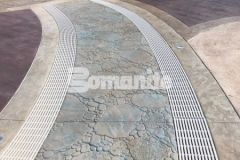 Bomanite Bomacron stamped concrete was expertly installed by our colleague, Harrington Bomanite, to include these serpentine drains that infiltrate storm water and minimize runoff while accentuating the decorative concrete decking at the Castaway Island water feature.